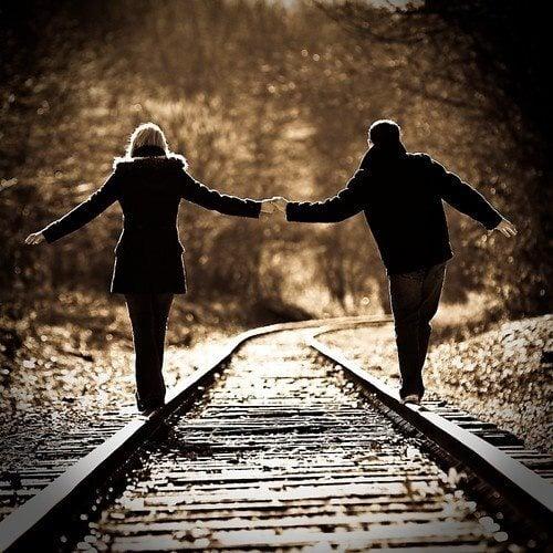 pareja caminando por las vías del tren tomados de las manos