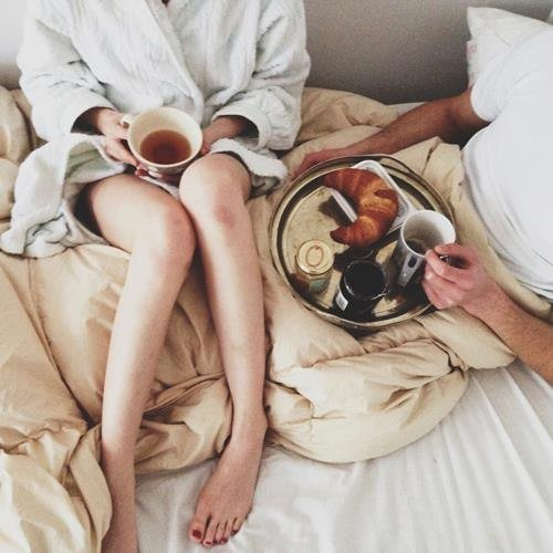 novios en la cama desayunando y tomando café