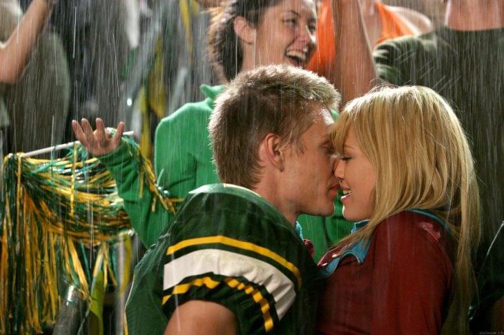 novios besandose bajo la lluvia