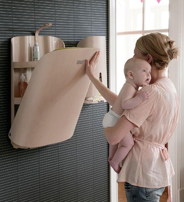 mujer con bebe en los brazos acomodando el cambiador de pañales