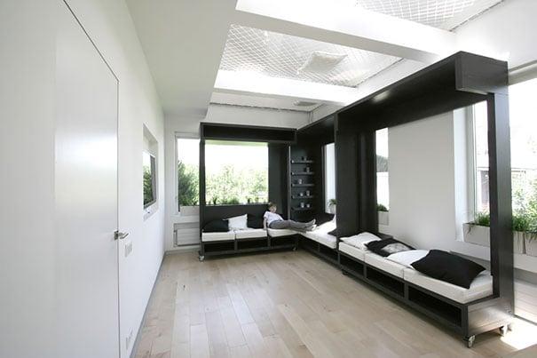 camas acomodadas de manera lineal en un gran cuarto