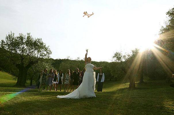 mujer en medio de un jardín lanzando un gato al aire para que sea atrapado por una multitud de mujeres
