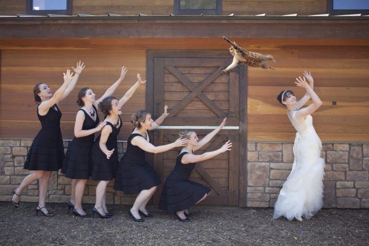 novia lanza a un gato aq sus damas de honor vestidas de negro afuera de un granero