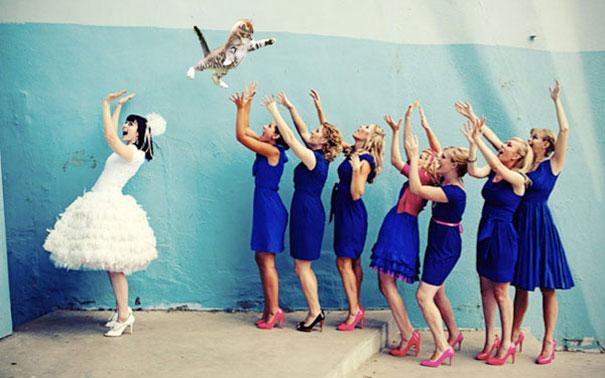 novia lanza a un gato a sus damas de honor vestidas de color azul rey mientras están en la calle esperando atrapar el ramo de la novia
