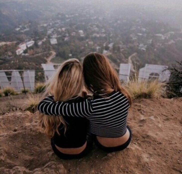 Chicas abrazándose sentadas en una colina
