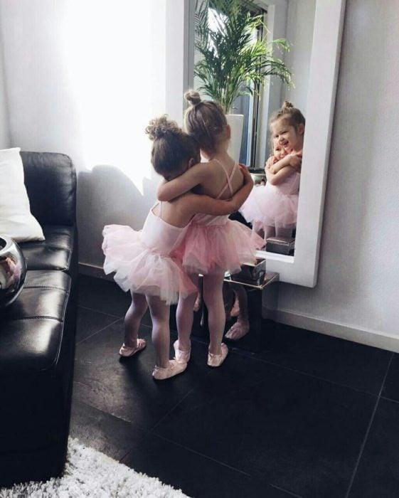 Niñas con vestido de bailarina abrazándose frente al espejo