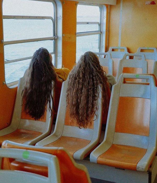 Chicas de cabello suelto y largo viajando en tren