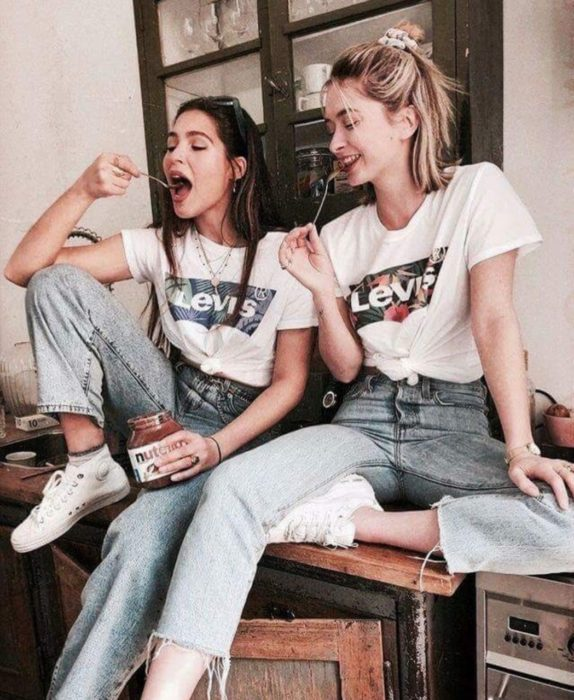 Chicas comiendo Nutella sentadas en escritorio
