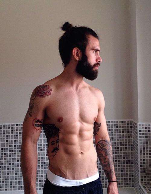 Hombre semidesnudo con barba y cola de caballo