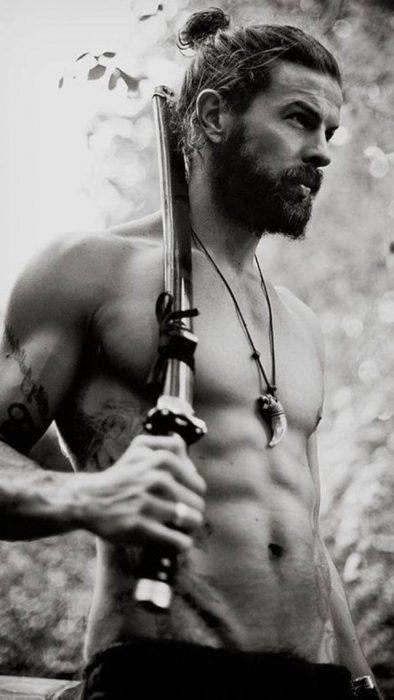 Hombre sin camisa con una espada