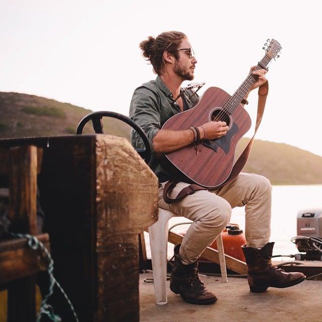 Hombre músico con barba al pie de un lago