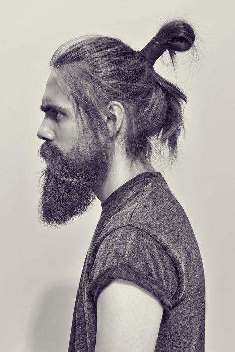 Un hombre hipster con peinado de samurái