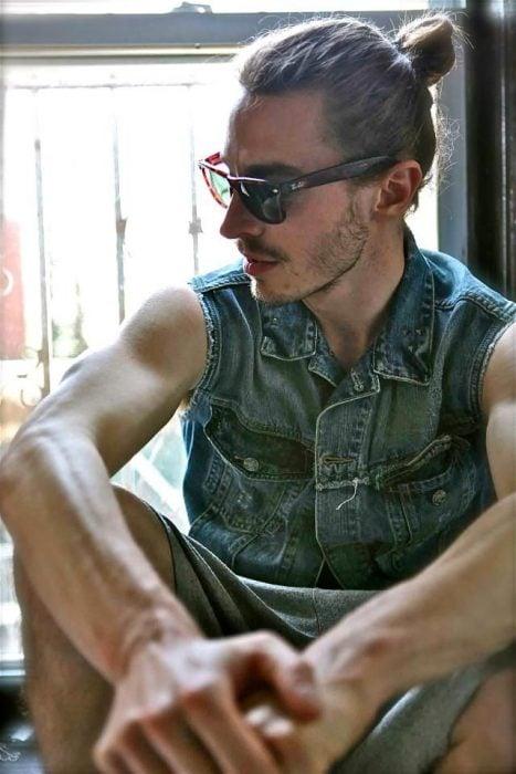 Hombre guapo con lentes de sol y chaleco de mezclilla