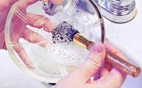 Recipiente con champú y brocha de maquillaje