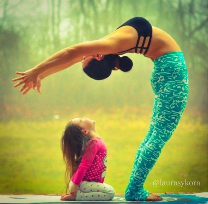 Woman stretching her body back and his daughter sitting behind her