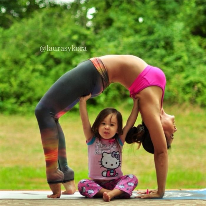 Girl under her mother practicing yoga