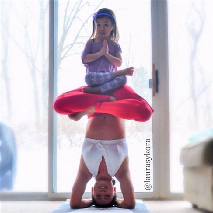 Paso de yoga mujer de cabeza y su hija sentada en su trasero