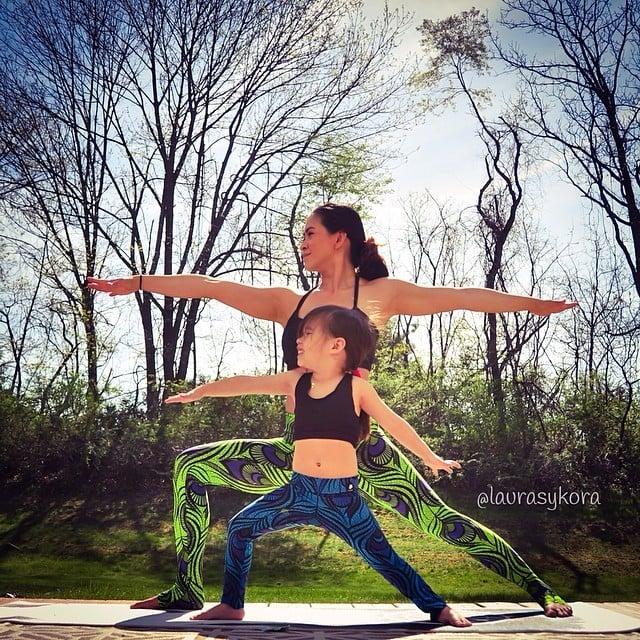 Madre e hija haciendo un split con los brazos de lado