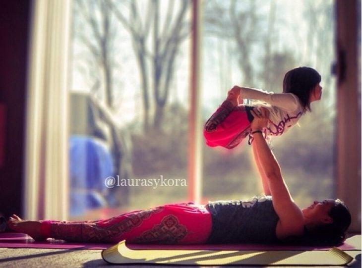 Mujer recostada en el suelo levantando a su hija