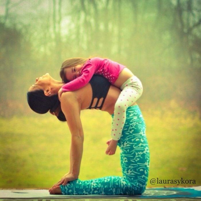 mujer hacia atrás tocando sus pies y con su hija sobre ella