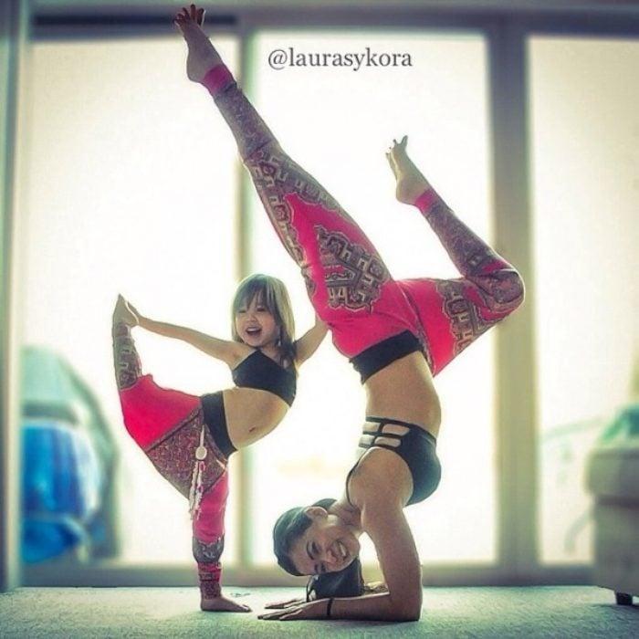 Madre e hija haciendo una pase de yoga con los pies hacia arriba