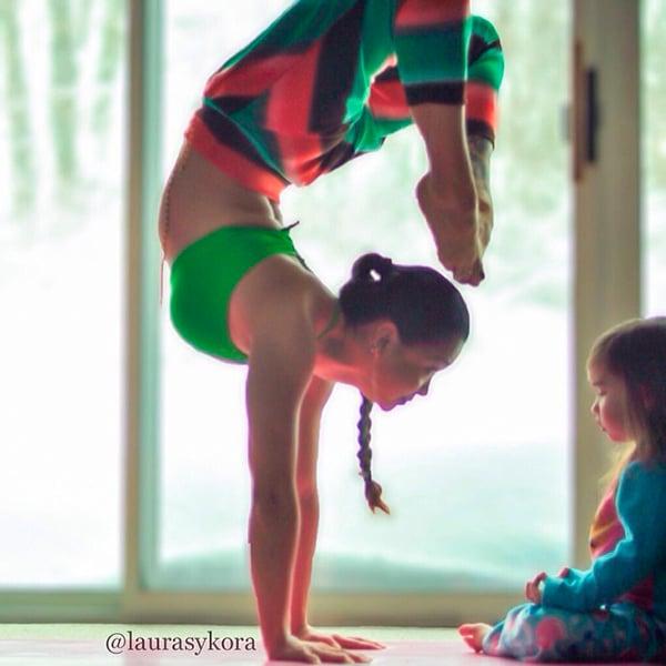 Mujer frente a su hija parada sobre sus manos