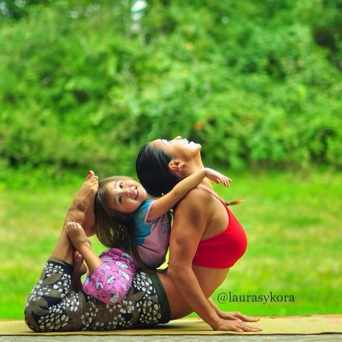 girl on her mother's legs complementing a step back yoga