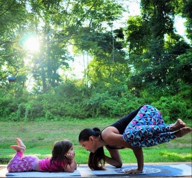 Madre e hija sobre un tapete practicando yoga