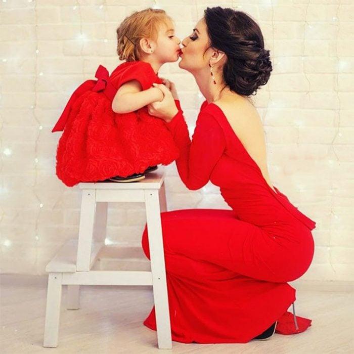 mamá besando a su hija que está arriba de un banquito