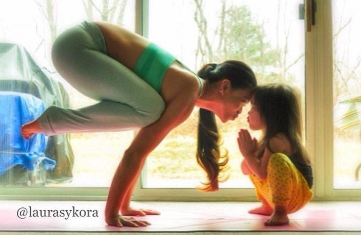 Madre recargada en el piso sobre sus manos y niña agachada intentando darse un beso