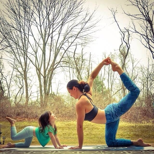 Mother and daughter practicing yoga outdoors