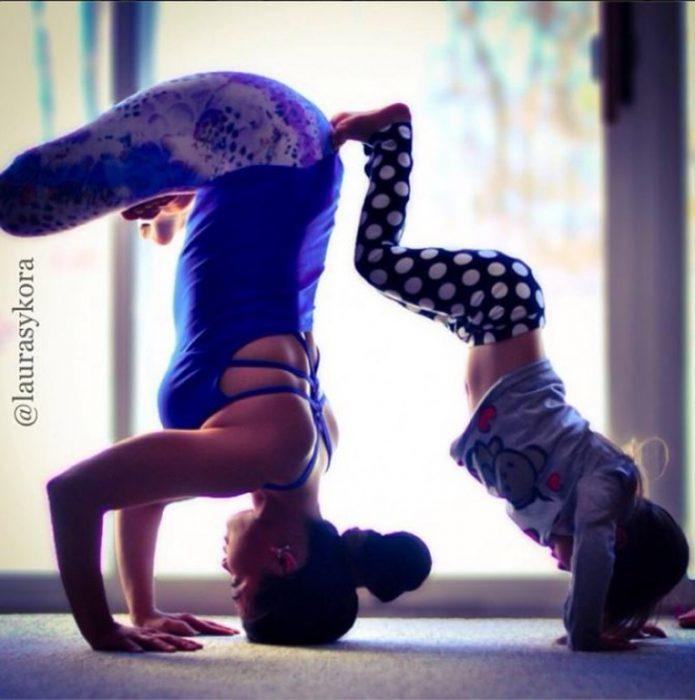 Madre e hija posando un paso de yoga de cabeza una recargada sobre la otra