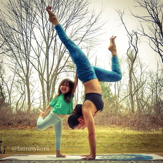 Woman on her hands and her daughter by lifting the right foot back