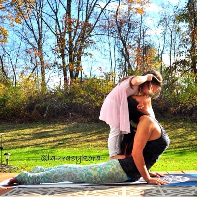 Madre e hija dándose un beso en un paso de yoga