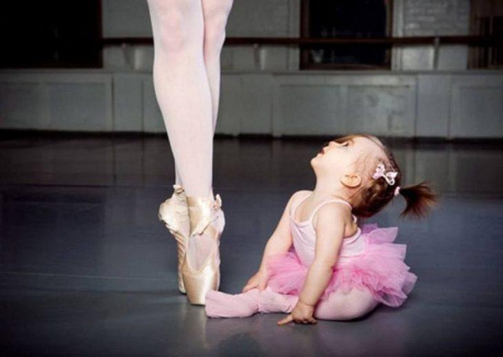 Niña vestida de ballet mirando hacia arriba viendo a su mamá