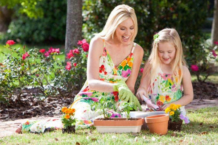 niñas y madres en un jardín arreglando las flores