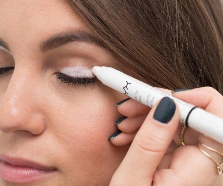 Cara de una mujer delineándose el parpado con un lápiz blanco