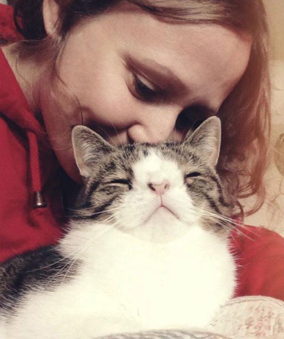 Monty bajo la cara de su ama recibiendo cariño