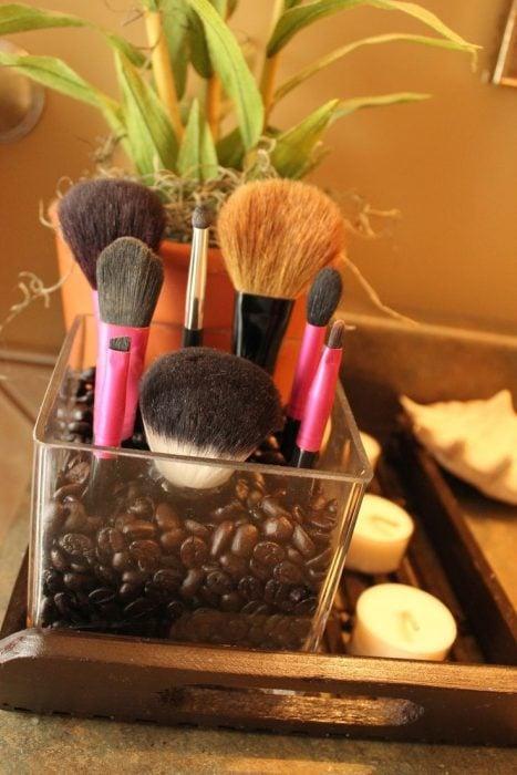Florero con granos de café y unas brochas de maquillaje dentro