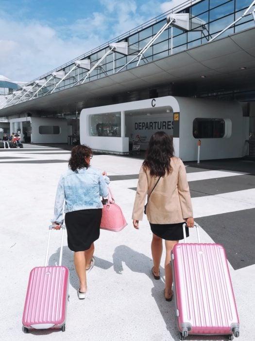 Madre e hija caminando con maletas