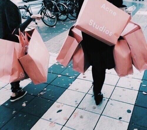 Mujeres caminando con bolsas rosas de compras
