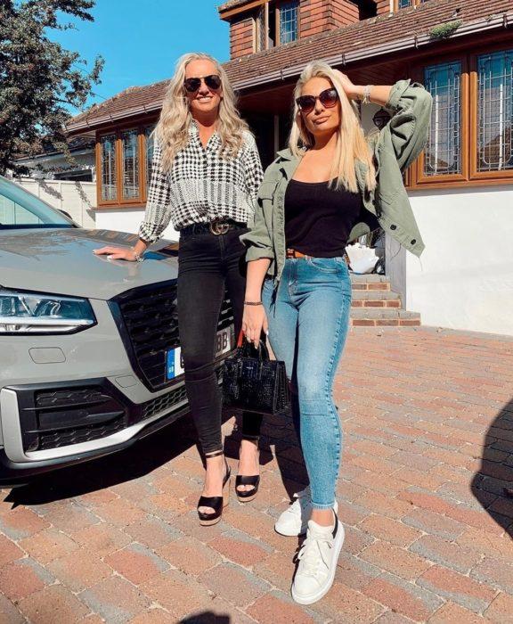 Madre e hija posando frente a un automóvil