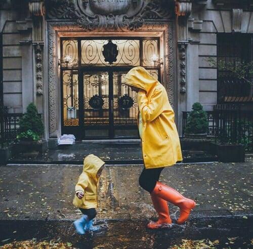 Madre e hija juegan en la lluvia con impermeables amarillos