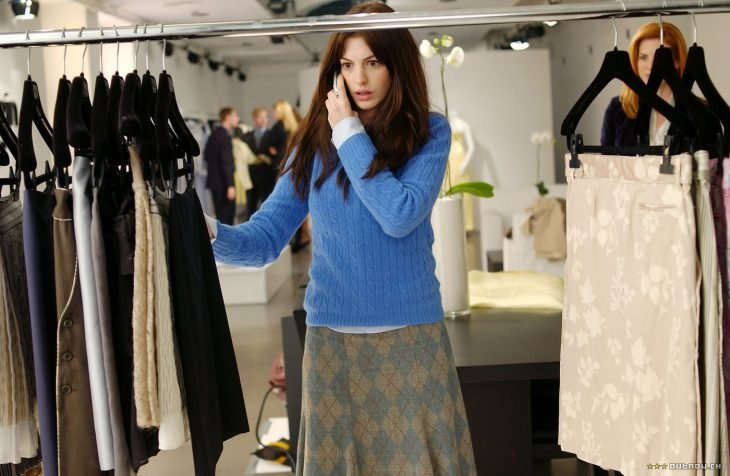mujer vestida con suéter azul y falda con rombos mirando ropa de un estante y hablando por celular