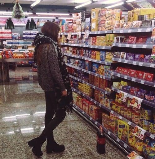 mujer frente a un estante de comida en el supermercado