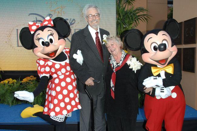 pareja de adultos mayores al lado de los personajes de Disney mimi y mickey mouse