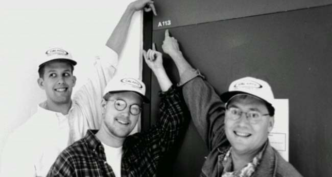 """trio de hombres señalado una puerta con el número """"A 113"""""""