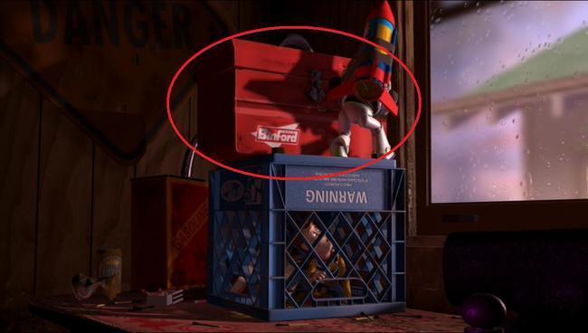 caja de herramientas colocada en la parte superior de una caja de leche mientras un muñeco con un cohete intenta sacar al juguete que esta bajo él
