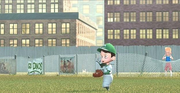 niño de cinco años jugando beisbol en un campo atrás de unos edificios