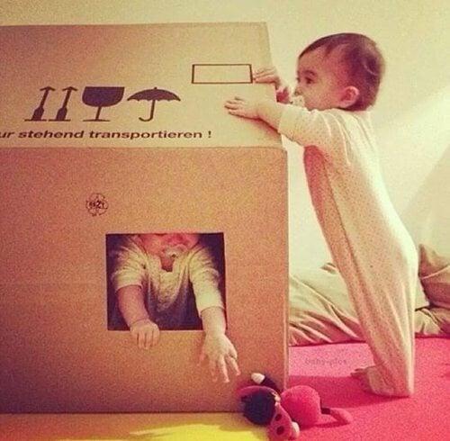 Niño envolviendo a su hermano en una caja